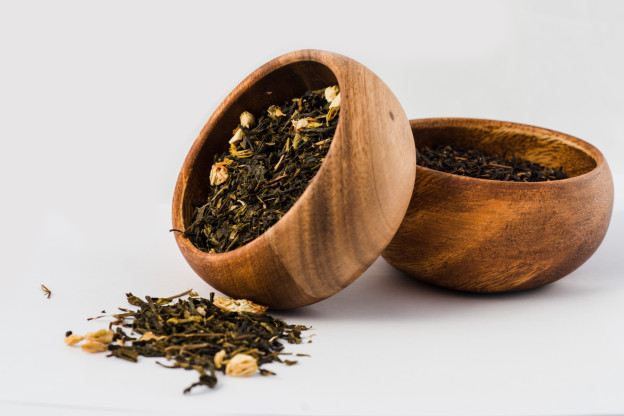 Green tea and black Tea in wooden bowls